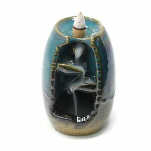Small Black And Teal Ceramic Back Flow Incense Burner With A Vase And Waterfall Design.